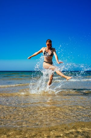 Splash. Young Woman Enjoying in water on the Beach. Summertime