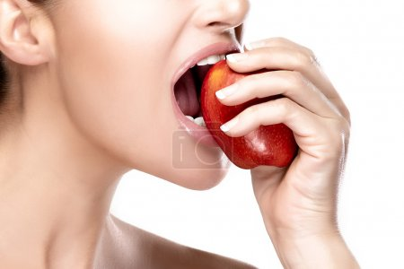 Photo for Closeup of beautiful and healthy mouth biting a red apple. Closeup portrait isolated on white background - Royalty Free Image