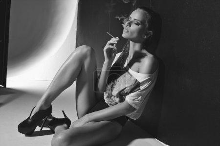 Fashion photo of sexy woman smoking a cigarette