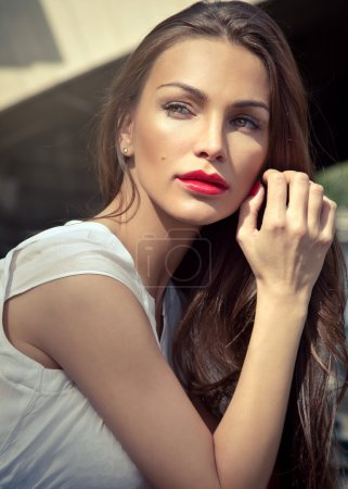 Attractive brunette with sunlight on her face. Beautiful summer