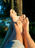 Foot of couple on hammock enjoying sun