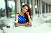 Beautiful smiling woman working on laptop