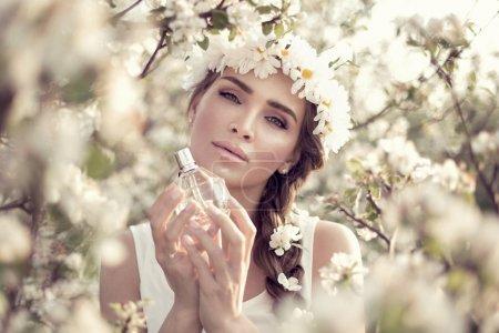 Photo pour Belle femme avec une bouteille de parfum - image libre de droit