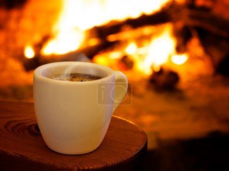Foto de Imagen horizontal de una taza de café caliente frente la chimenea - Imagen libre de derechos