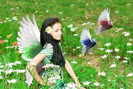 Photo pour Beau jeune ange céleste aux ailes assises sur l'herbe regardant avec une douce expression - image libre de droit