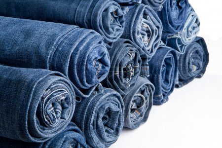 Photo for Roll blue denim jeans arranged in stack - Royalty Free Image