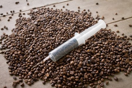 Photo for Coffee seed in syringe, mean to caffeine addiction - Royalty Free Image