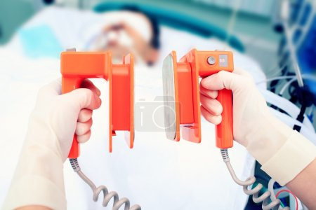 Defibrillator electrodes in hands. Work in the ICU...