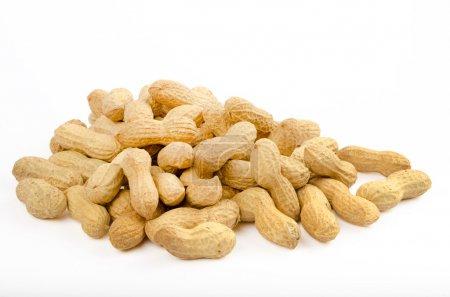 viele Erdnüsse in Schalen auf weißem Hintergrund