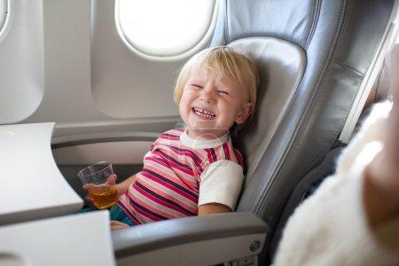 Photo pour Pleurer enfant avec du jus dans l'avion - image libre de droit