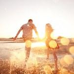 Happy couple running on the beach...