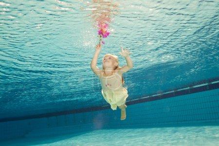 Photo pour Fille dans la piscine sous l'eau avec une fleur - image libre de droit