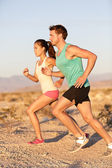 Runners couple running in trail run outside