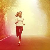 Running woman jogging on road