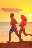 Jogging couple running exercising at sunset beach
