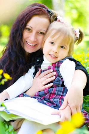 Photo for Mother with daughter read a book on the meadow - Royalty Free Image