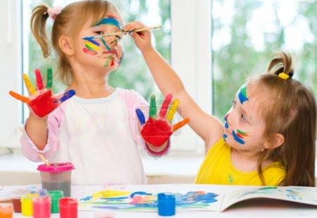 Photo pour Deux petites filles peignant au pinceau et peintures colorées - image libre de droit