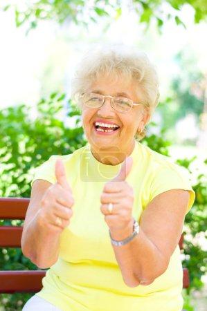 Photo pour Souriant femme âgée tenant son pouce à l'extérieur - image libre de droit