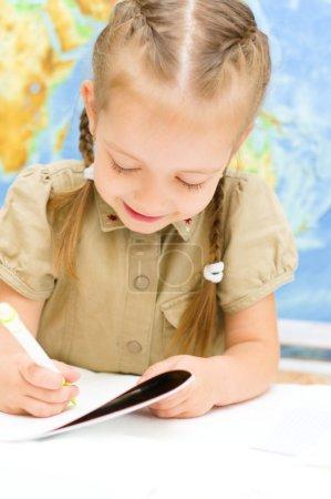 Photo pour Petite fille mignonne écrit à l'aide d'un stylo en face de la carte du monde en maternelle - image libre de droit