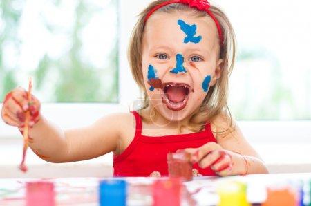Photo pour Petite fille peinture avec pinceau et peintures colorées - image libre de droit