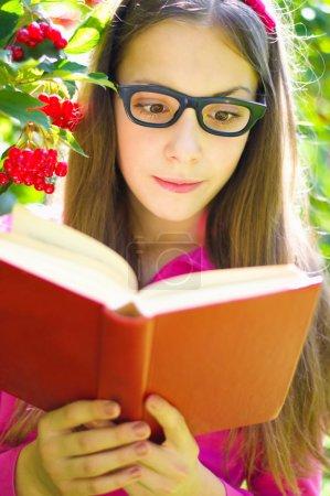Photo pour Adolescente mignonne lit un livre tout en portant des lunettes à l'extérieur - image libre de droit