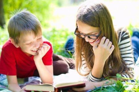 Photo pour Les enfants lisent ensemble en profitant d'un livre posé sur l'herbe à l'extérieur - image libre de droit