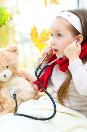 Photo pour Petite fille examine son ours en peluche en utilisant stéthoscope - image libre de droit