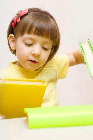 Photo for Cute little girl play with books while sitting at table - Royalty Free Image