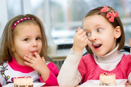 Photo for Cute little girls are eating cake in parlor - Royalty Free Image
