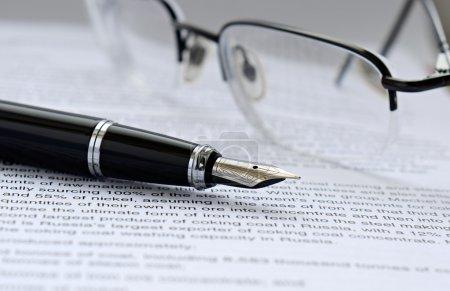 Photo pour Stylo et lunettes sur le papier avec texte - image libre de droit