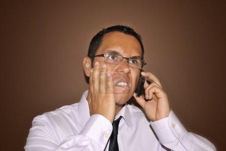 Photo pour Très en colère jeune homme d'affaires parlant au téléphone - image libre de droit
