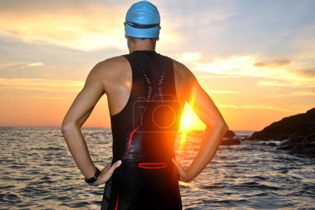 Young athlete triathlon in front of a sunrise over...