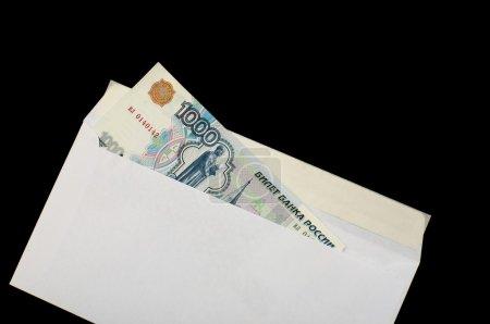 Photo pour Roubles russes dans une enveloppe blanche, isolés sur un fond noir - image libre de droit