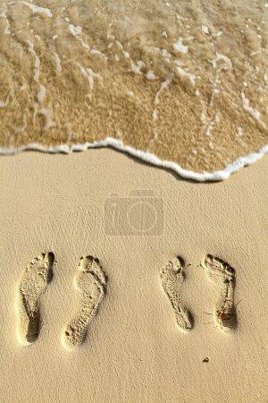 Photo pour Deux paires de pas sur la plage de sable corallien - image libre de droit