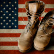 Grunge US Army boots on sandy american flag backgr...