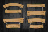Brown wooden vector banners and ribbons hanging on ropes on wooden background
