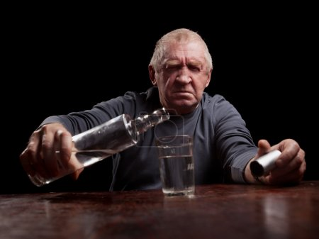 Photo for Portrait senior man pouring white alcohol in a glass - Royalty Free Image