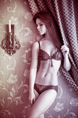 sexy young woman in lingerie posing in bedroom.