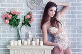 sexy young woman in retro lingerie posing against decorate brick