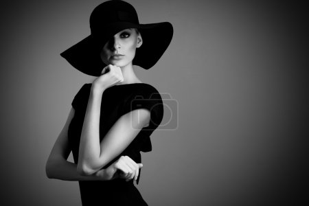 High fashion portrait of elegant woman in black and white hat and dress