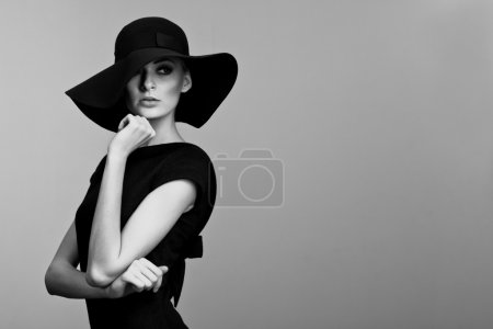 Photo pour High fashion portrait of elegant woman in black and white hat and dress. Studio shot - image libre de droit