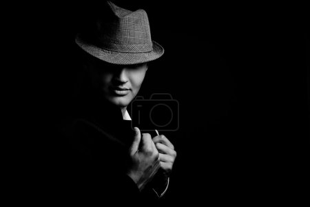 low key portrait of young gangster with hat in the darkness.