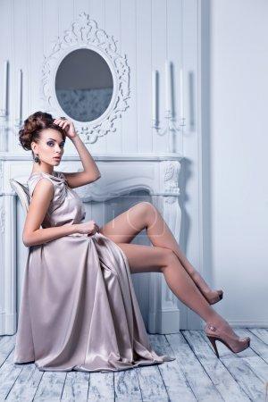 Photo pour Prise de vue de mode de jeune belle femme en robe de soie magnifique assis dans un fauteuil antique - image libre de droit