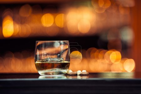 Photo for Glass of whiskey on a wooden table bar on the background of bright lights of the bar - Royalty Free Image