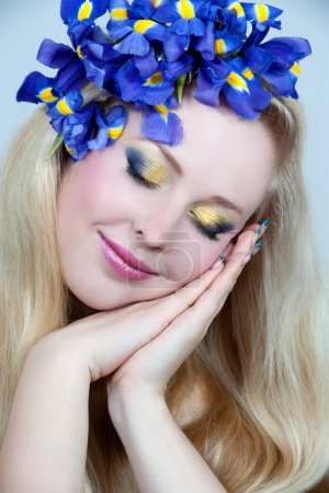 Beautiful young blonde woman with iris flower