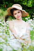 Beautiful woman enjoying daisy field, pretty girl relaxing outdoor, having fun, holding plant, happy young lady and spring green nature, harmony concept