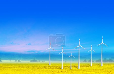 Wind turbines farm green electricity on yellow field