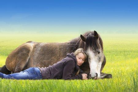 Photo pour Fille et cheval couché et dormir sur le champ, journée d'été ensoleillée, contre le ciel bleu - image libre de droit