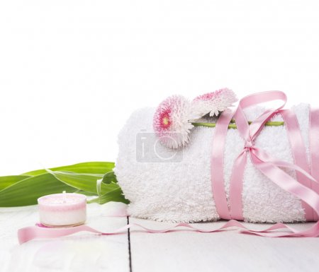 Rolled up towel, tied with Pink Ribbon with daisy flowers on wooden table,isolated