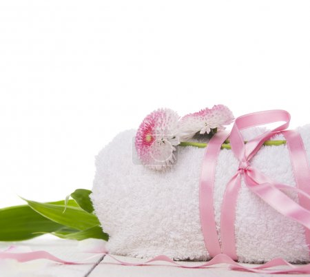 Rolled up towel,silk ribbon,daisies flowers and bamboo leaves spa,isolated,